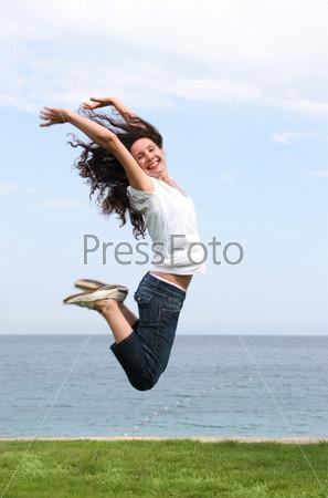 Счастливая девушка прыгает вверх подняв руки  на фоне морского побережья