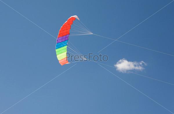 Высоко в голубом небе парит красочный парашют