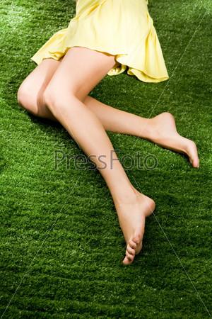 Фотография на тему Крупный план красивых стройных ног на фоне зеленой травы