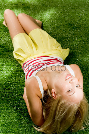 Красивая девушка лежит на зеленой траве и смотрит вверх