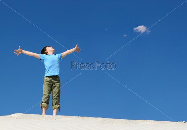 Мальчик раскинув руки стоит на песке и смотрит вверх на фоне синего неба