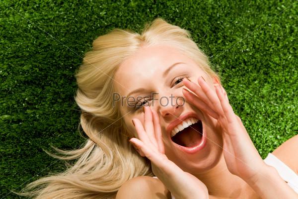 Красивая девушка лежа на зеленой траве кричит сложив руки у рта