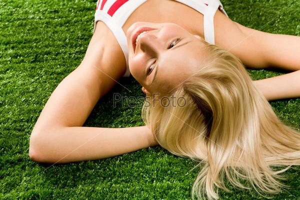 Красивая блондинка лежит на зеленой траве закинув руки за голову