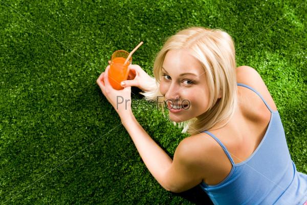 Красивая блондинка в голубой майке лежит на зеленой траве держа в руках бокал с напитком
