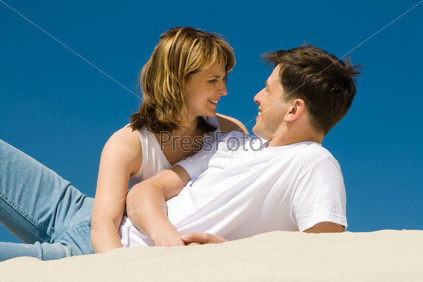 Молодая пара лежит на песке обнявшись и глядя друг на друга влюбленными взглядами
