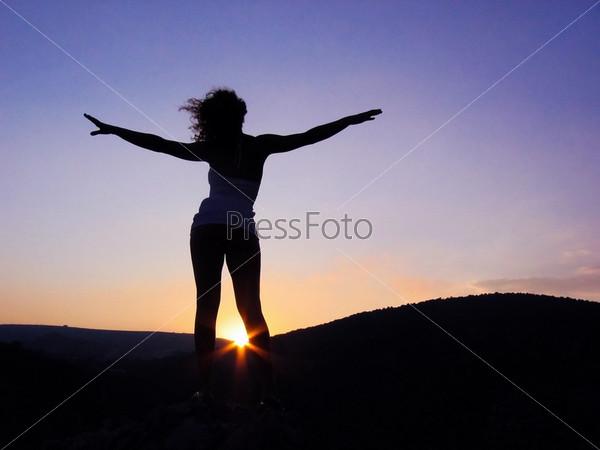 Красивая девушка стоит на фоне заходящего солнца раскинув руки