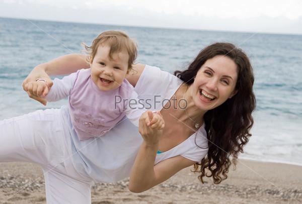 Позитивная мама играет со своей дочкой на берегу моря