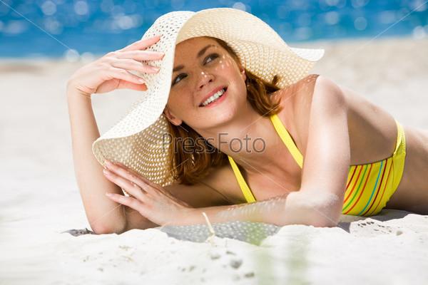 Очаровательная девушка в белой шляпе лежит на песке и улыбается