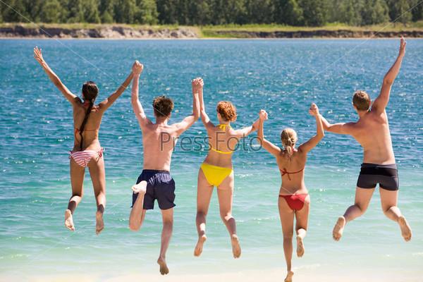 Компания молодых людей прыгает в воду