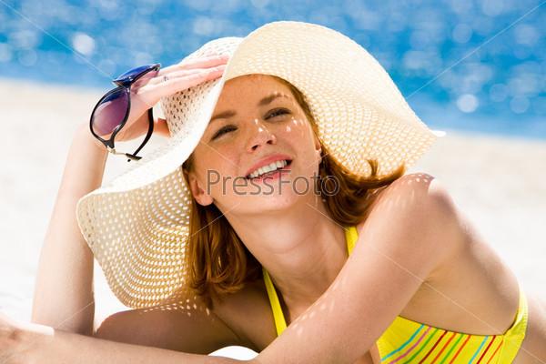 Красивая девушка в шляпе отдыхает на пляже