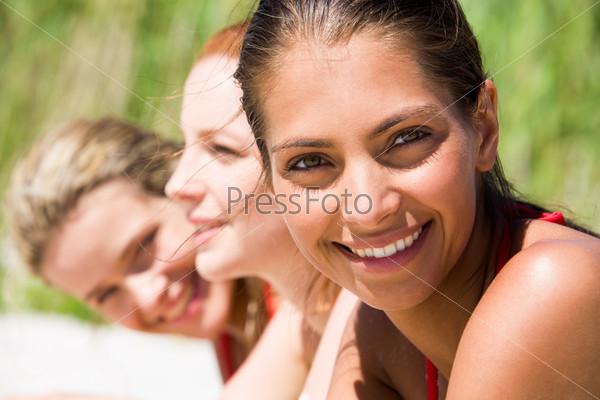 Красивая загорелая девушка улыбается в камеру на фоне своих подруг