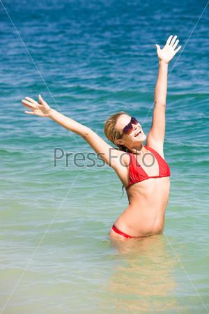 Красивая девушка стоит в воде вытянув руки вверх и смеется