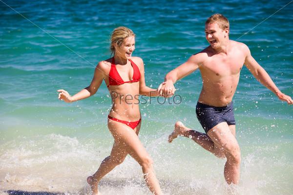 Молодая пара бежит по побережью держась за руки