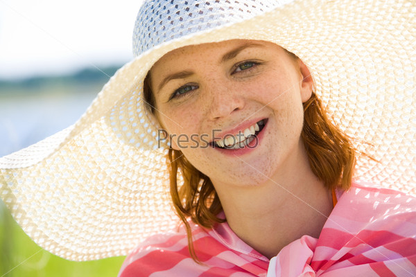 Рыжая девушка в большой белой шляпе смотрит в камеру и улыбается