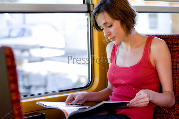 Девушка едет в вагоне поезда и читает журнал у окна
