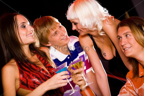 Компания молодых людей общается на вечеринке держа в руках коктейли с напитками