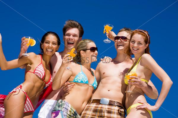 Компания красивых загорелых молодых людей стоит на песке обнявшись и смеясь