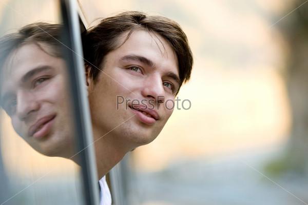 Молодой человек высунувшись из окна вагона смотрит в сторону и улыбается