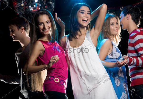 Две очаровательные девушки танцкют в ночном клубе