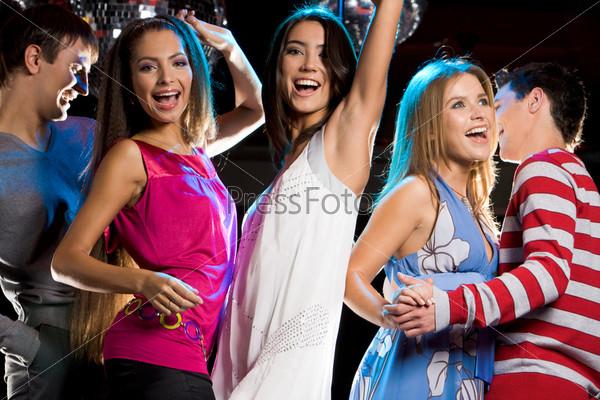 Компания молодых людей танцующих в ночном клубе