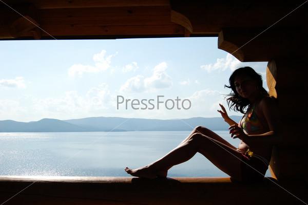 Девушка в купальнике сидит на фоне моря