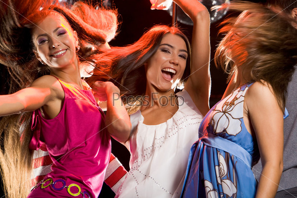 Три девушки энергично танцуют в ночном клубе и смеются