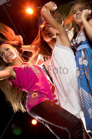 Три подруги активно танцуют на танцполе в ночном клубе