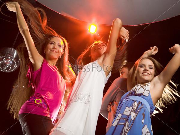 Вид снизу трех красивых девушех танцующих на вечеринке