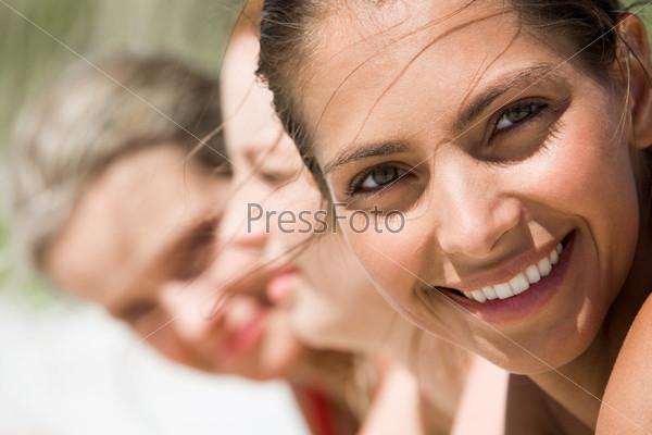 Красивая девушка с очаровательной улыбкой смотрит в камеру на фоне своих подруг