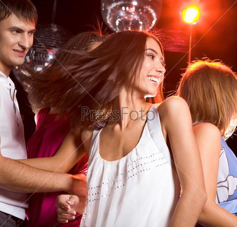 Энергичная девушка танцует в клубе в окружении своих друзей