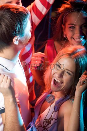 Радостные лица молодых людей танцующих на вечеринке