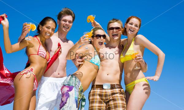 Веселая компания стоит на песчаном пляже держа в руках коктейли