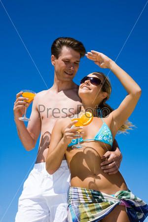 Красивая пара обнявшись стоит на пляже держа в руках бокалы