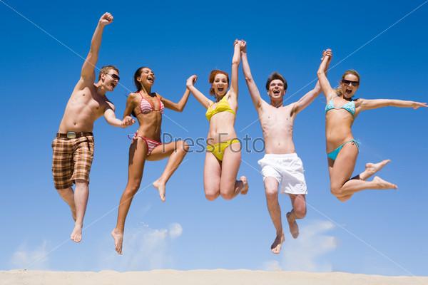Веселая компния на пляже подпрыгивает вверх держась за руки