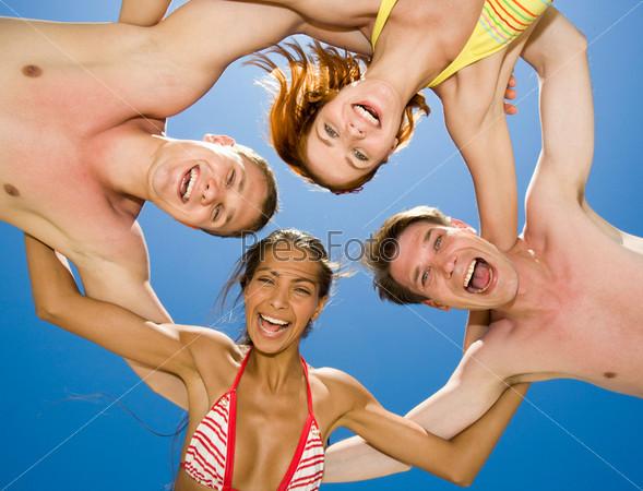 Компания молодых людей в купальниках обнявшись смотрит вниз в камеру и смеется