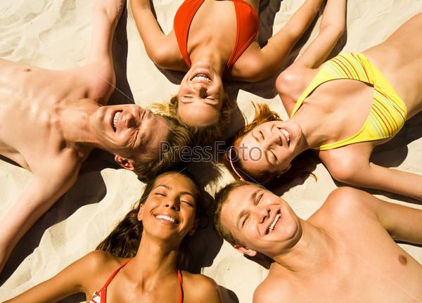 Компания молодых людей лежит на пляже