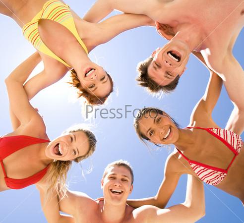 Фотография на тему Компания веселых людей стоит обнявшись на фоне неба