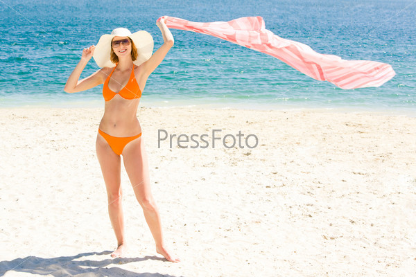 Стройная девушка стоит на побережье держа в руках развевающийся платок