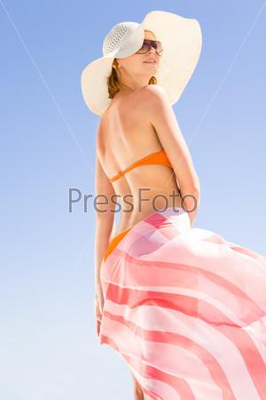 Вид снизу девушки на пляже с развевающимся парео в руках