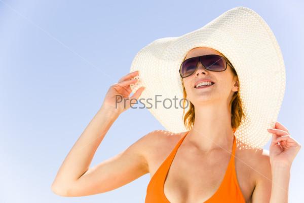 Девушка в шляпе и купальнике смотрит вверх на фоне неба