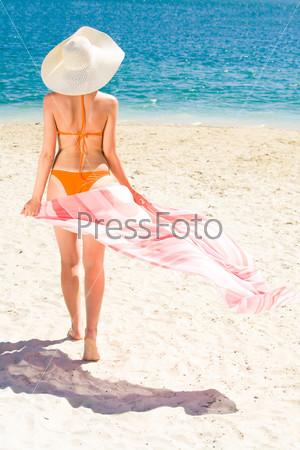 Девушка идущая по песку в сторону моря