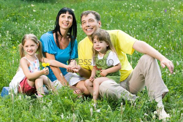 Дружная семья сидит на поляне