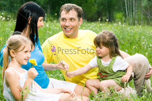 Дружная семья общается сидя на поляне