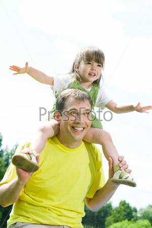 Девочка сидит на плечах у папы, раскинув руки на фоне зеленого леса