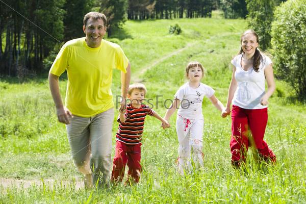 Счастливая семья держась за руки бежит вдоль леса