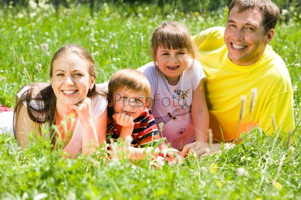 Дружная семья лежит на поляне и улыбается