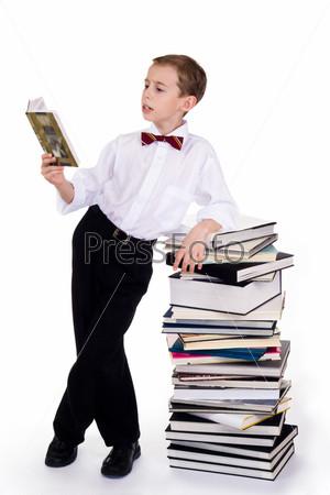 Интеллигентный ребенок стоит с раскрытым учебником опираясь на стопку книг