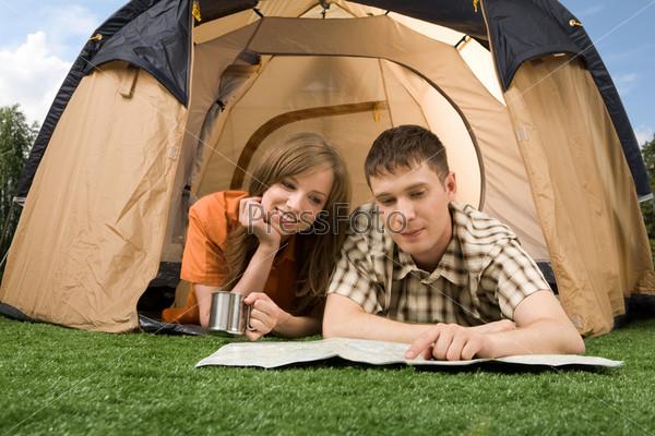Пара путешественников лежит на траве возле палатки и смотритт в карту