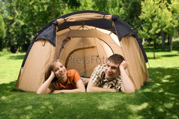 Молодая пара лежит на траве возле палатки и улыбается в камеру