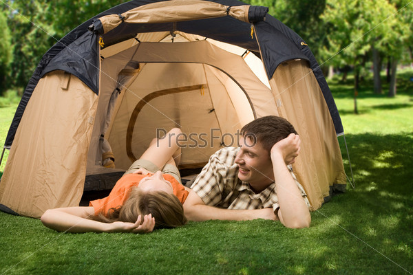 Молодой человек лежит на траве рядом со своей подругой на природе